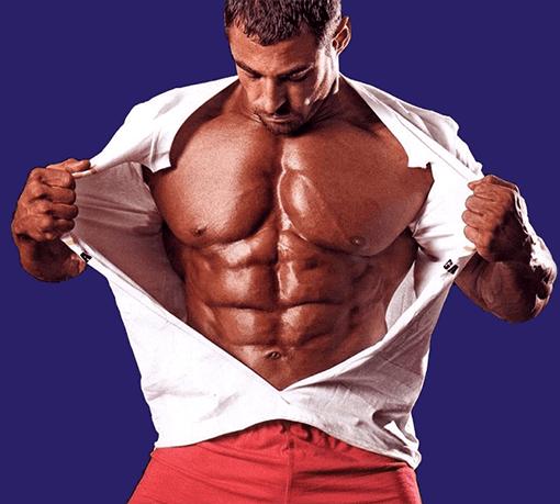 Мъж със златен загар разкъсва дрехата си, показвайки своята покачена чиста мускулна маса, след като е вземал Анавор 3 месеца наред.